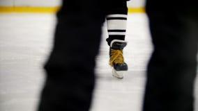 Παίκτης χόκεϋ που οδηγά στον πάγο που κάνει πατινάζ κατά τη διάρκεια της κατάρτισης Άποψη των ποδιών απόθεμα βίντεο