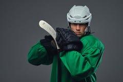 Παίκτης χόκεϋ που φορά το πράσινο προστατευτικό εργαλείο και το άσπρο κράνος που στέκονται με το ραβδί χόκεϋ απομονωμένος σε έναν Στοκ Φωτογραφίες