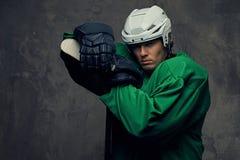 Παίκτης χόκεϋ που φορά το πράσινο προστατευτικό εργαλείο και το άσπρο κράνος που στέκονται με το ραβδί χόκεϋ απομονωμένος σε έναν Στοκ εικόνες με δικαίωμα ελεύθερης χρήσης