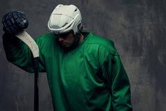 Παίκτης χόκεϋ που φορά το πράσινο προστατευτικό εργαλείο και το άσπρο κράνος που στέκονται με το ραβδί χόκεϋ απομονωμένος σε έναν Στοκ Εικόνες