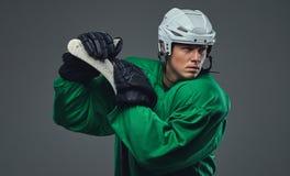 Παίκτης χόκεϋ που φορά το πράσινο προστατευτικό εργαλείο και το άσπρο κράνος που στέκονται με το ραβδί χόκεϋ απομονωμένος σε έναν Στοκ εικόνα με δικαίωμα ελεύθερης χρήσης