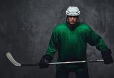 Παίκτης χόκεϋ που φορά το πράσινο προστατευτικό εργαλείο και το άσπρο κράνος που στέκονται με το ραβδί χόκεϋ απομονωμένος σε έναν Στοκ φωτογραφίες με δικαίωμα ελεύθερης χρήσης