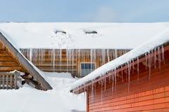 Παγάκια και χιόνι σε ένα παλαιό ξύλινο εξοχικό σπίτι Στοκ Εικόνα