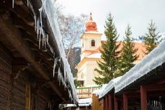 Παγάκια και χιόνι σε ένα παλαιό ξύλινο εξοχικό σπίτι Στοκ Φωτογραφίες