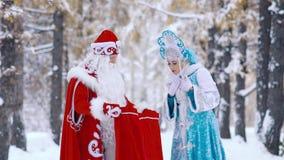 Παγετός πατέρων Moroz Ded που παρουσιάζει στο κορίτσι χιονιού Snegurochka νέα δώρα έτους απόθεμα βίντεο
