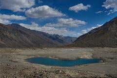 Παγετώδης λίμνη υψηλών βουνών, στενόμακρη νερού επιφάνεια νερού χρώματος σωμάτων φωτεινή μπλε στη μέση της κοιλάδας βουνών με τις Στοκ Εικόνες