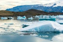 Παγετώδης λιμνοθάλασσα στην Ισλανδία, νεφελώδης καιρός, βουνά στον ορίζοντα Η παγετώδης λίμνη απεικονίζει τον ουρανό Στοκ Εικόνα