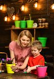 Παγιοποιήστε την έννοια Λίγη μητέρα βοήθειας παιδιών παγιοποιεί το λουλούδι Η μητέρα και ο γιος παγιοποιούν την ανάπτυξη εγκαταστ στοκ φωτογραφίες