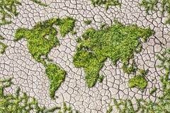 Παγκόσμιος χάρτης οικολογίας από τη χλόη στο ραγισμένο γήινο υπόβαθρο στοκ εικόνα