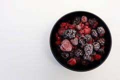 Παγωμένα μούρα στο μαύρο κύπελλο στην άσπρη επιφάνεια Στοκ Εικόνες