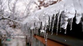 Παγωμένα παγάκια στην εστίαση από μια στέγη στοκ εικόνα