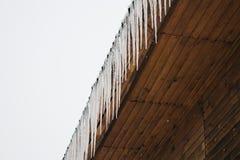 παγωμένα παγάκια στη στέγη του ξύλινου σπιτιού, ξύλινο μέγαρο τελευταίων ορόφων Παγωμένη σκηνή καιρικού χειμώνα στοκ φωτογραφία