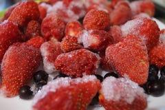 Παγωμένες φράουλες και μαύρες σταφίδες στα κομμάτια του πάγου και του παγετού σε ένα πιάτο στοκ φωτογραφία