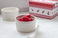 Παγωμένες φράουλες σε ένα άσπρο πιάτο σε ένα άσπρο τραπεζομάντιλο κοντά στο κιβώτιο Χριστουγέννων Στοκ Εικόνες