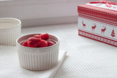 Παγωμένες φράουλες σε ένα άσπρο πιάτο σε ένα άσπρο τραπεζομάντιλο κοντά στο κιβώτιο Χριστουγέννων Στοκ φωτογραφία με δικαίωμα ελεύθερης χρήσης