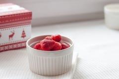 Παγωμένες φράουλες σε ένα άσπρο πιάτο σε ένα άσπρο τραπεζομάντιλο κοντά στο κιβώτιο Χριστουγέννων Στοκ Φωτογραφία
