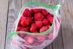 Παγωμένες φράουλες σε μια πλαστική τσάντα σε ένα ξύλινο υπόβαθρο Στοκ εικόνες με δικαίωμα ελεύθερης χρήσης