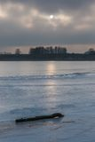 Παγωμένη λίμνη στην ανατολή ή το ηλιοβασίλεμα Χειμερινό ήρεμο τοπίο Στοκ Εικόνα
