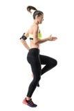 Παγωμένη κίνηση του κατάλληλου θηλυκού αθλητικού δρομέα που κάνει την υψηλή άσκηση προθέρμανσης γονάτων Στοκ Εικόνες