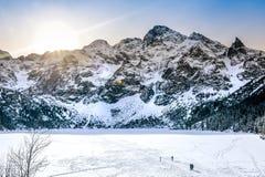 Παγωμένη λίμνη μπροστά από τα χιονώδη βουνά Χειμώνας κατά τη διάρκεια της ανατολής στοκ φωτογραφία με δικαίωμα ελεύθερης χρήσης