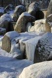 Παγωμένος καταρράκτης με τους χιονισμένους λίθους Στοκ Φωτογραφίες