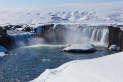 Παγωμένος καταρράκτης με το σαφές μπλε νερό Στοκ Εικόνες