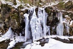 Παγωμένος καταρράκτης ποταμών που διαμορφώνεται κατά τη διάρκεια του κρύου χειμώνα στα βουνά της Ρουμανίας Στοκ Φωτογραφίες