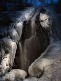 Παγωμένος καταρράκτης χειμερινής άποψης νύχτας, παγάκια και παγωμένοι λίθοι στο ρεύμα. Στοκ Εικόνα