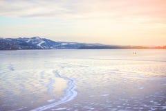 Παγωμένος ποταμός και απόμακρα βουνά Στοκ Φωτογραφίες