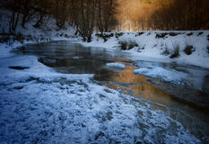Παγωμένος ποταμός το χειμώνα στο ηλιοβασίλεμα Στοκ Φωτογραφία
