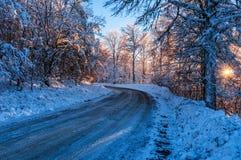 Παγωμένος δρόμος σε ένα χιονώδες δάσος στο ηλιοβασίλεμα Στοκ Εικόνες