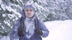 Παγωμένο άτομο στο χιόνι, που περπατά μέσω των ξύλων με ένα σακίδιο πλάτης απόθεμα βίντεο