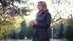 Παγωμένο κορίτσι σε ένα πάρκο φθινοπώρου φιλμ μικρού μήκους