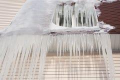 παγωμένο παράθυρο Διοχέτευση παγακιών στην καφετιά στέγη Έννοια κρύου καιρού Στοκ Εικόνα
