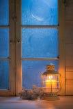 Παγωμένο παράθυρο τη νύχτα με το κάψιμο του κεριού για τα Χριστούγεννα Στοκ Εικόνα