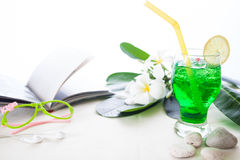 Παγωμένο πράσινο ποτό χρώματος στο άσπρο υπόβαθρο με το λουλούδι plumeria Στοκ εικόνες με δικαίωμα ελεύθερης χρήσης