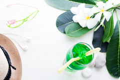 Παγωμένο πράσινο ποτό χρώματος στο άσπρο υπόβαθρο με το λουλούδι plumeria Στοκ Φωτογραφία