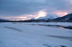 Παγωμένο τοπίο ποταμών με την ηλιόλουστες ρόδινες πυράκτωση και την αντανάκλαση Στοκ Εικόνες