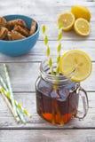 Παγωμένο τσάι με τις φέτες λεμονιών και τα μπισκότα τσιπ σμέουρων σε αγροτικό Στοκ Φωτογραφία