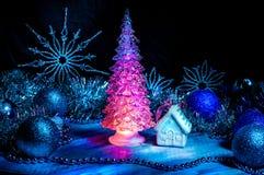 Παγωμένο χριστουγεννιάτικο δέντρο που καίγεται με το κόκκινο φως σε ένα μπλε υπόβαθρο Στοκ Φωτογραφία