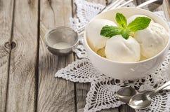 Παγωτό βανίλιας με τα φύλλα μεντών στο άσπρο κύπελλο στο αγροτικό ξύλινο υπόβαθρο Στοκ φωτογραφία με δικαίωμα ελεύθερης χρήσης