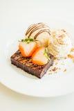 Παγωτό βανίλιας με brownie σοκολάτας το κέικ με τη φράουλα επάνω στοκ εικόνες