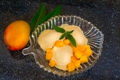 Παγωτό μάγκο με τις φρέσκες φέτες μάγκο με τη μέντα φύλλων σε ένα πιάτο γυαλιού Στοκ Εικόνες