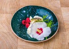 Παγωτό με ένα λουλούδι Ένα μπλε στρογγυλό κεραμικό πιάτο με το άσπρο παγωτό Ένα όμορφο κρύο επιδόρπιο σε έναν ξύλινο Στοκ φωτογραφία με δικαίωμα ελεύθερης χρήσης