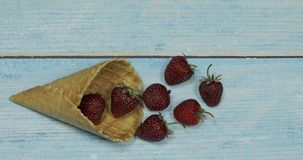 Παγωτό μούρων Μούρα της φράουλας σε μια βάφλα σε ένα μπλε ξύλινο υπόβαθρο απόθεμα βίντεο