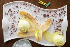 Παγωτό φρούτων με τη φρέσκια μπανάνα που ψεκάζεται με τη σοκολάτα στο άσπρο πιάτο Στοκ Φωτογραφίες