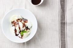 Παγωτό φυστικιώνβανίλιας andμε τη σάλτσα σοκολάτας σε ένα κύπελλο σε ένα πιάτο σε ένα κλωστοϋφαντουργικό προϊόν λινού Στοκ εικόνα με δικαίωμα ελεύθερης χρήσης