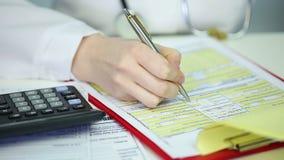 Παθολόγος γυναικών που συμπληρώνει τα έγγραφα, υπολογίζοντας τις δαπάνες ασφάλειας υγείας του ασθενή απόθεμα βίντεο