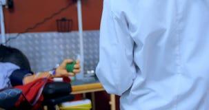 Παθολόγος που ελέγχει το ανώτερο άτομο που δίνει το αίμα 4k απόθεμα βίντεο