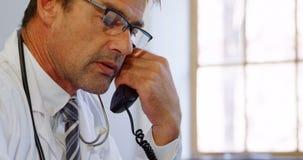 Παθολόγος που χρησιμοποιεί το lap-top μιλώντας στη γραμμή εδάφους στο γραφείο στην κλινική 4k φιλμ μικρού μήκους